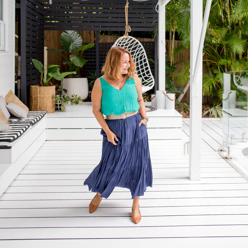 Karen is wearing our Rachael technical cami in green tucked into Sophie technical maxi skirt in steel blue with neutral belt and tan shoes.