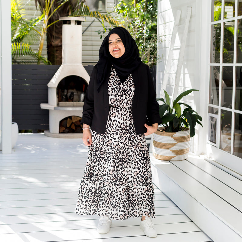 Faaiza in our Whitney midi dress - animal print and our Karen scuba jacket - black paired with white sneakers