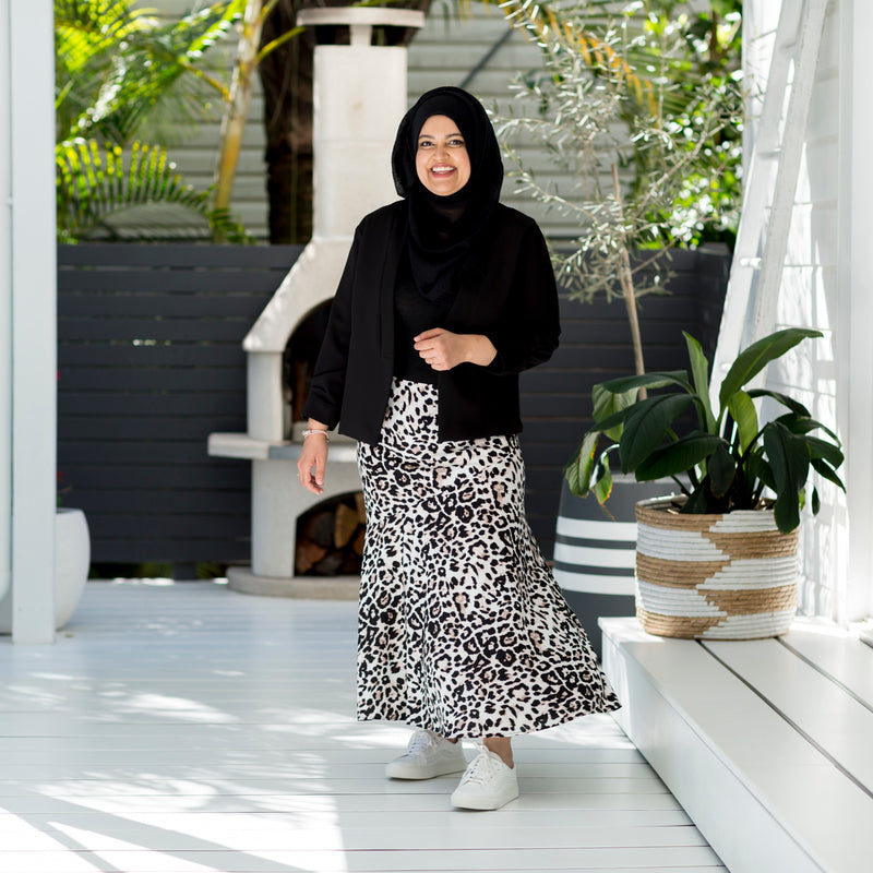 Faaiza wearing our Kutira midi skirt - animal print with the Rachael technical cami - black and our  Karen scuba jacket - black with white sneakers