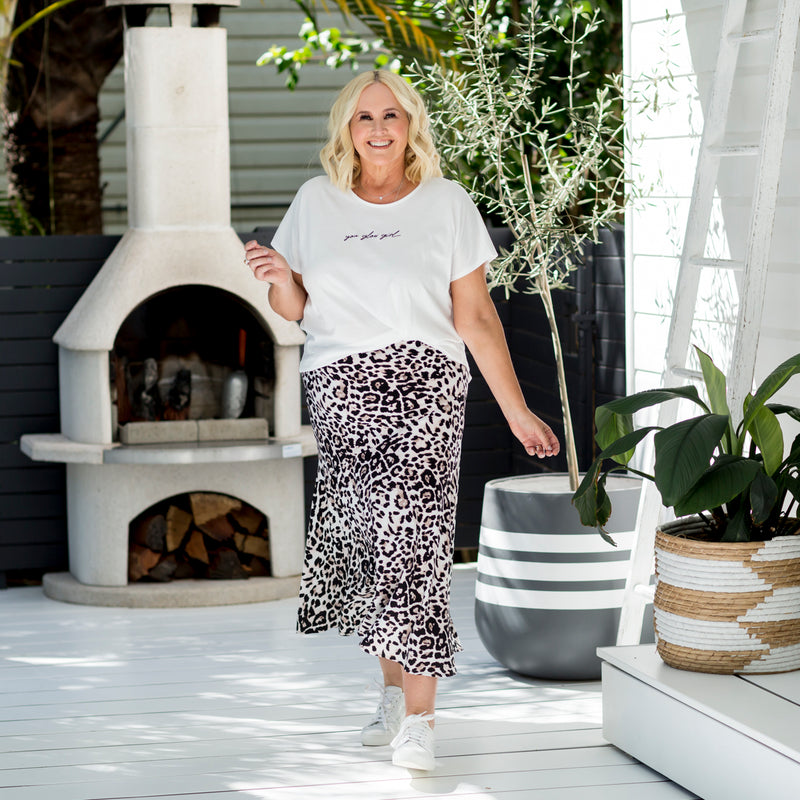 Nikki wearing our Kutira midi skirt - animal print with our Tanya relaxed tee - white and white sneakers