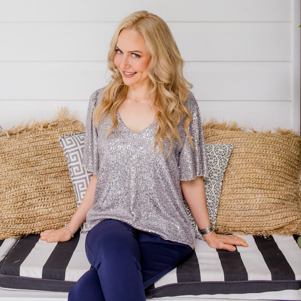 Lisa is wearing our Caitlin sequin blouse in silver with Laura pants in navy