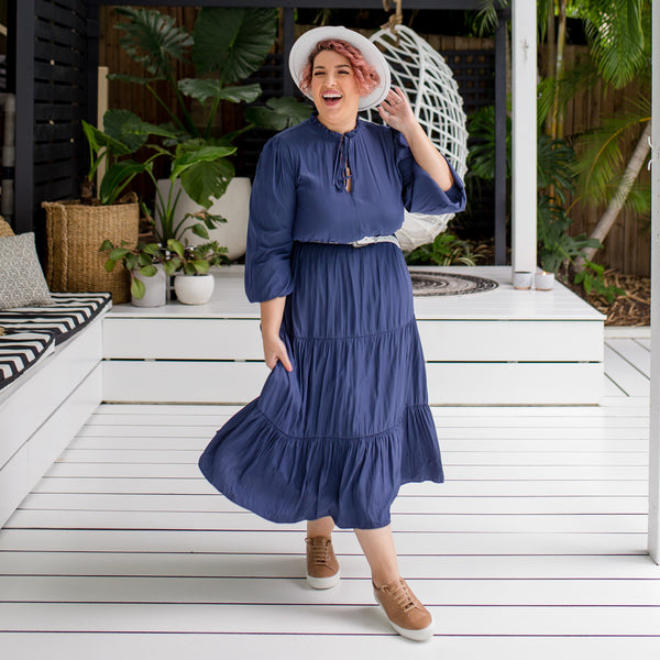 Jo wearing our Edwina technical billow-sleeve midi dress in steel blue tied at the neck with a white belt and white fedora. She has tied this look together with some brown sneakers.