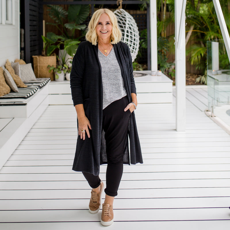 Nikki wearing our Jalena longline cardigan in black over our Jenny knit in grey with our Suzie Ponte pants in black. She has styled this with our brown sneakers and gold jewellery.