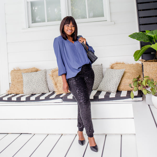 Sonia is wearing our Felicity blouse in steel blue with Dorothy sequin pants in black with high black heels and a small black hand bag over her shoulder
