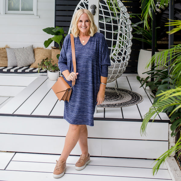 Nikki wearing our navy marl Wendy lightweight sweater dress with a brown crossbody bag and brown sneakers.