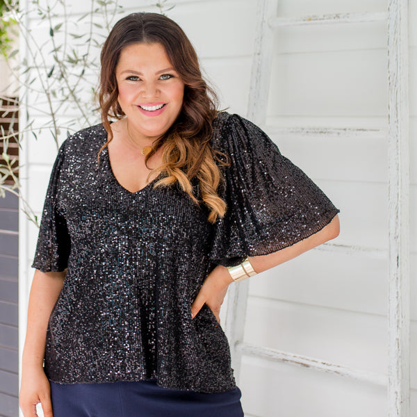 Stacey is wearing our Caitlin sequin blouse in black with Laura pants in navy