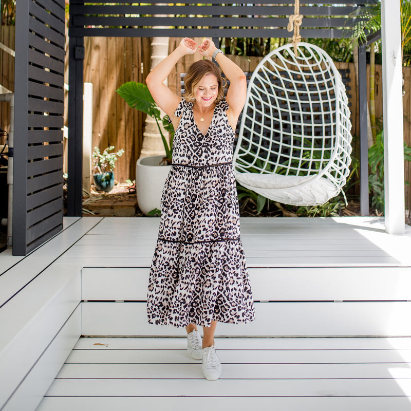 Bec wearing our Bev animal print dress that features tie up shoulders with white sneakers