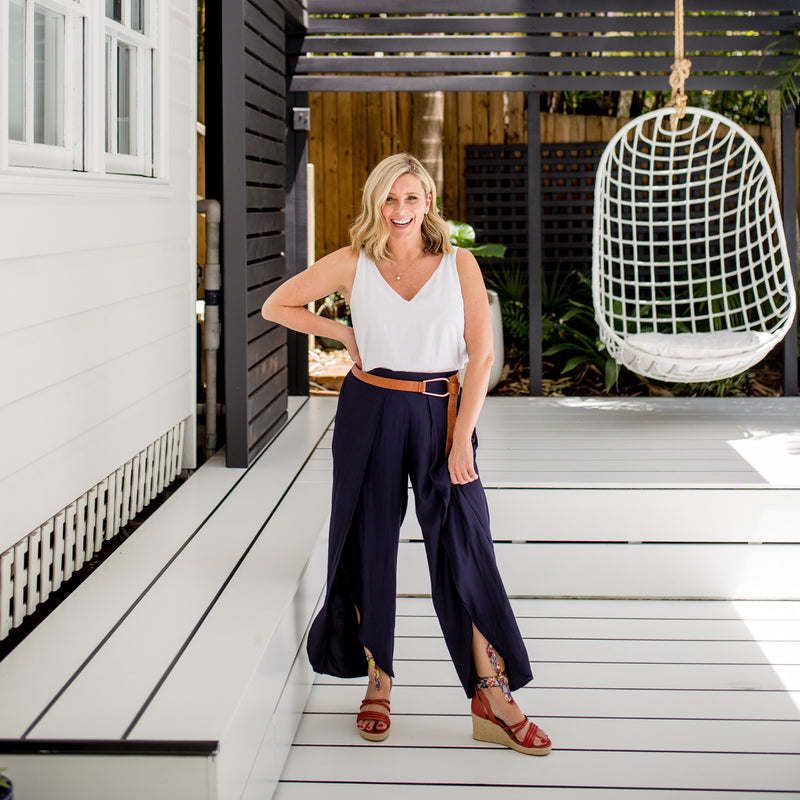 Brooke wearing our Rachael technical cami in white with our navy maria split pants and a brown belt.