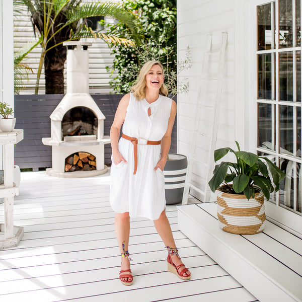 Brooke wearing our Katy sleeveless technical shirt-dress in white with a tan belt and red heels.