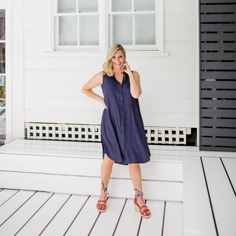 Brooke wearing our Katy technical sleeveless shirt dress in navy with red wedges
