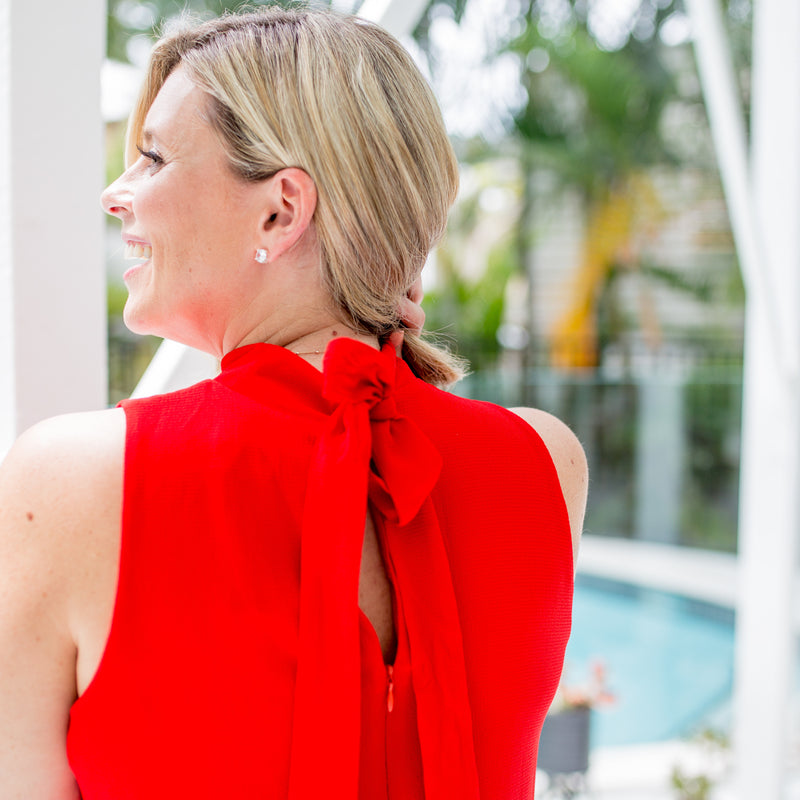 Brooke wearing red Sonia playsuit. Image shows tie detailing at the back of playsuit.