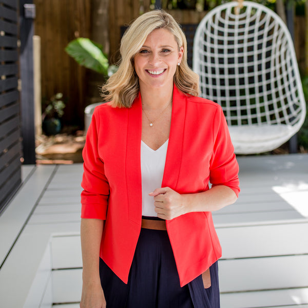 Brooke wearing our Karen scuba jacket in coral over our white cami and navy pants.