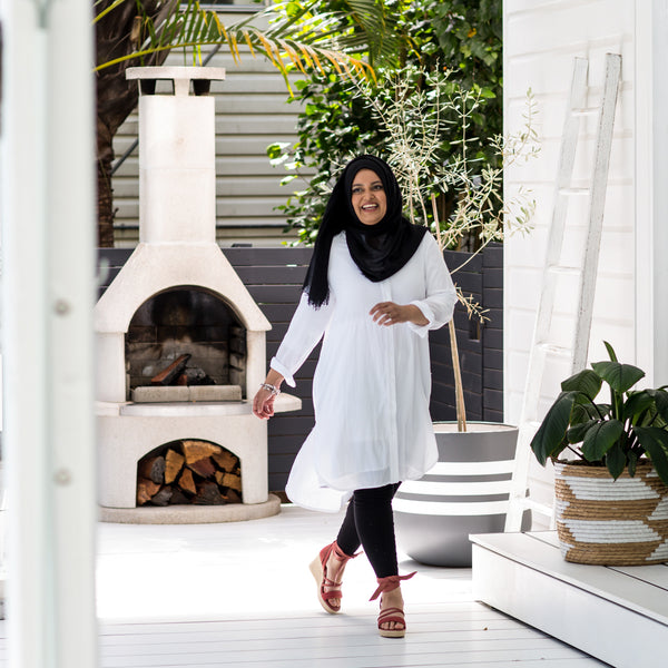 Faaiza wearing our Danielle technical shirt dress in white with a black Hijab, blck leggings and red heels.
