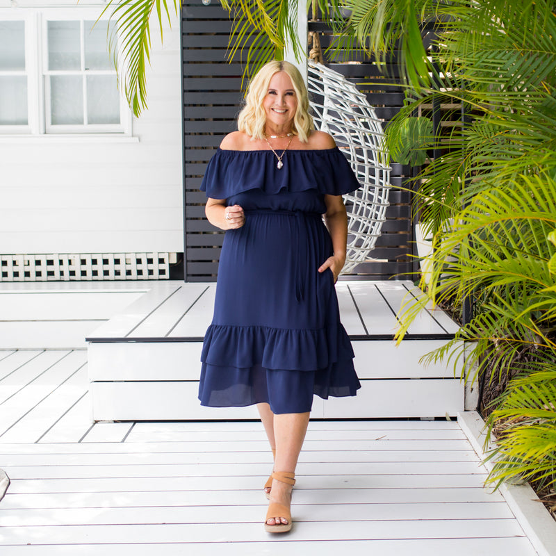 Nikki wearing our natalie off-the-shoulder dress in navy with tan heels.