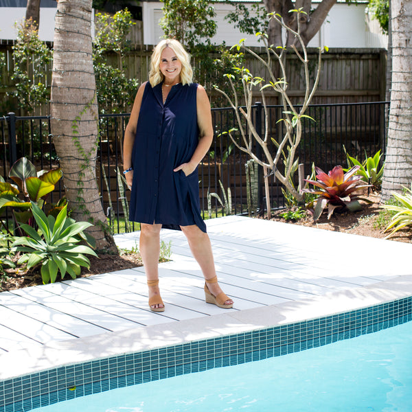 Nikki wearing our Katy technical sleeveless shirt dress in navy with tanned wedges