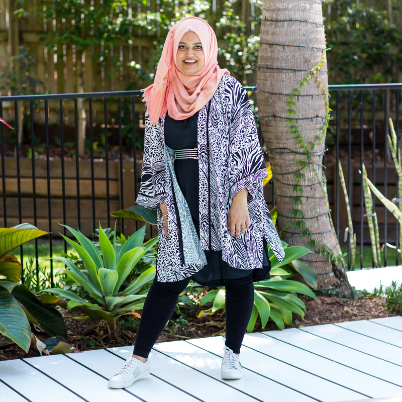 Faaiza wearing our Krista duster in safari print over our Katy sleeveless shirt dress with black leggings and a pink Hijab.