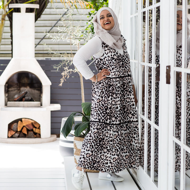 Faaiza wearing our Bev tie shoulder animal print dress over a white long sleeve tee, white sneakers  and neutral Hijab