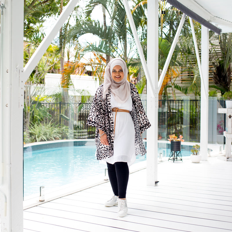 Faaiza wearing our Katy sleeveless technical shirt-dress in white with black leggings underneath, our peta animal print duster, a tan belt and a natural hijab.