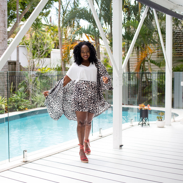 Sonia wearing our white Alexa tee tucked into our Gillian animal print shorts. This is paired with our Peta animal print duster and red wedges.