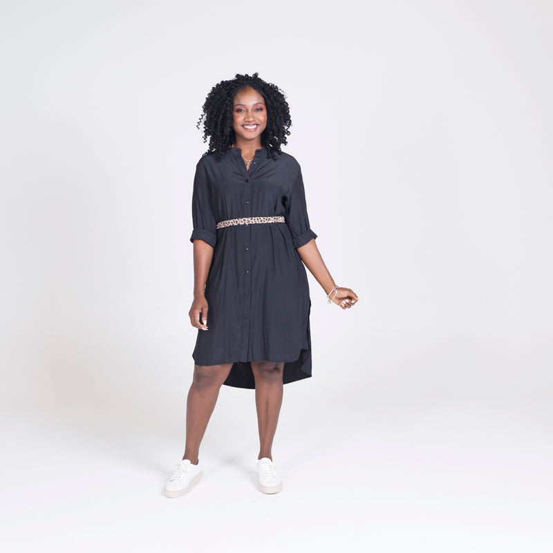 Danielle technical shirt dress in black, styled with a leopard print belt tied around the waist and white sneakers.