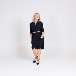Danielle technical shirt dress in black, styled with a tan belt tied around the waist and black strappy heels.