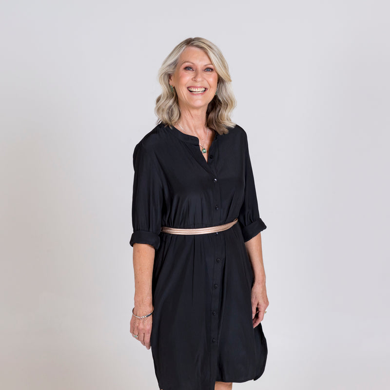 Danielle technical shirt dress in black, styled with a tan belt tied around the waist.