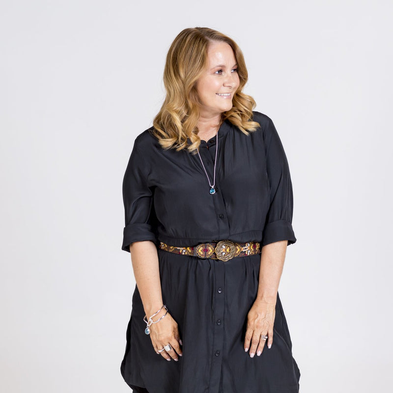 Danielle technical shirt dress in black, styled with a leopard print belt tied around the waist.