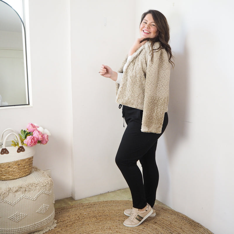 Renee faux fur jacket champagne worn over the shoulders with Sharon relaxed long sleeve tee white underneath, Suzie ponte jogger pant black and sneakers.