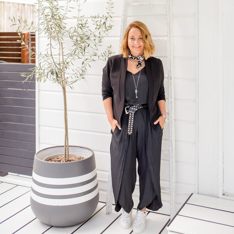 Karen wearing our Karen scuba jacket - black with our Maria technical split pant - black, Rachael technical cami - black,  Nik scarf/wrap - animal print, a long necklace, belt and white sneakers