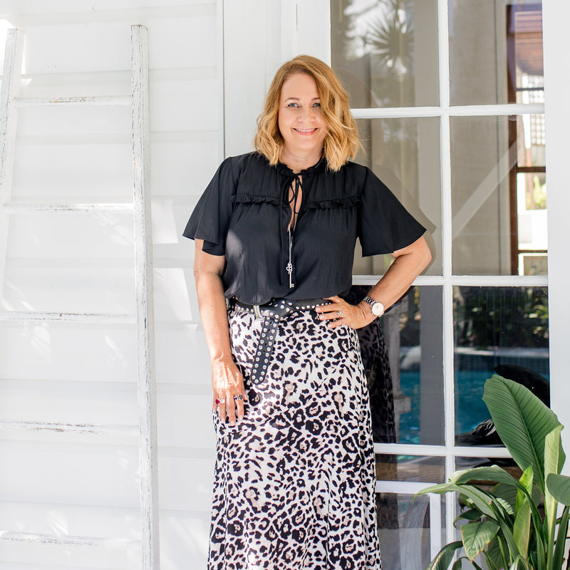 Karen wearing our Kim technical blouse - black and our Kutira midi skirt - animal print with a belt and a long necklace