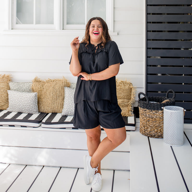 Stacey wearing our  Kim technical blouse - black with our Bec technical shorts - black and white sneakers