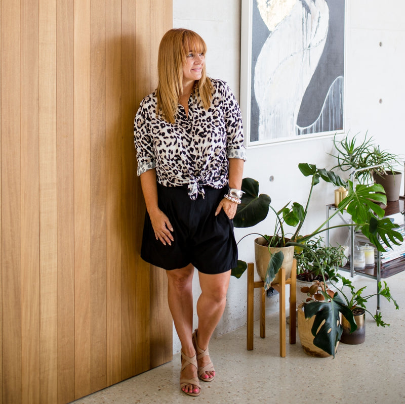 Karen wearing our Simone animal print shirt tied up over our Bec shorts in black with a nude strappy heel.