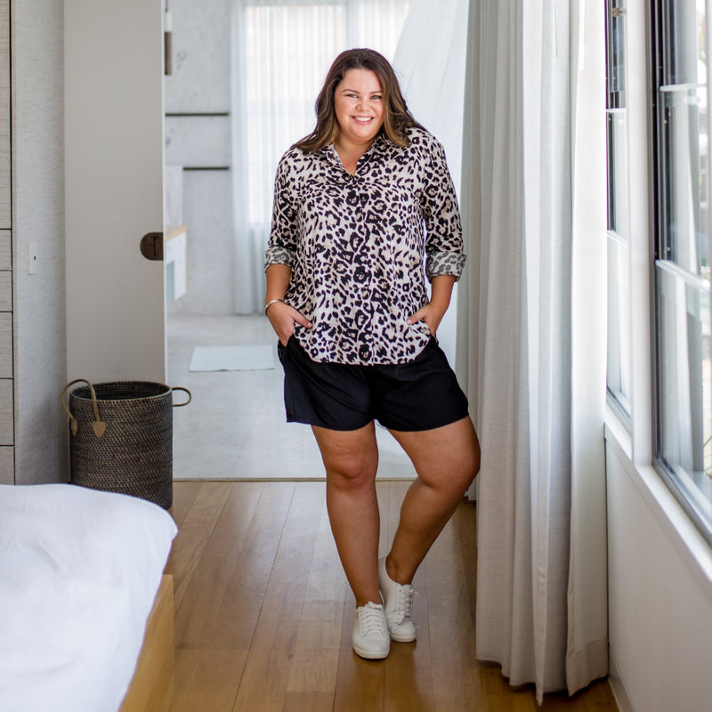 Stacey wearing our simone animal print shirt with the sleeves rolled up over our Bec shorts with white sneakers