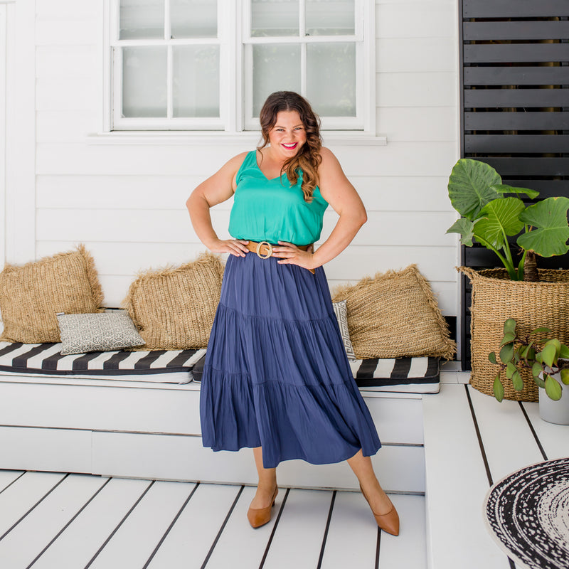 Stacey is wearing our Rachael technical cami in green tucked into Sophie technical maxi skirt in steel blue with tan belt and tan shoes.