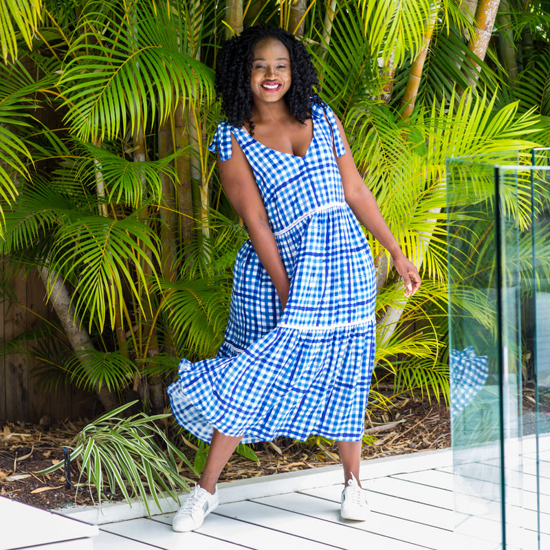 Sonia wearing our Vanessa tie-shoulder dress in gingham with white sneakers.