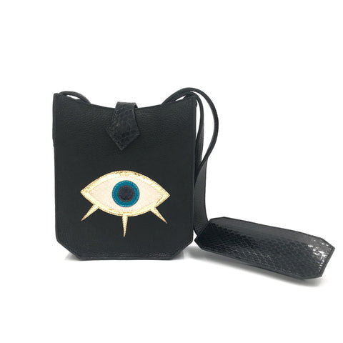Evil eye bag keeps you protected all day and all night. Motif and gusset are adorned with snake skin. Features adjustable strap, back phone pocket, and microfiber pink lining.