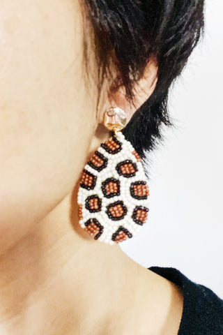 woman wearing dangling leopard print earrings made from seed beads