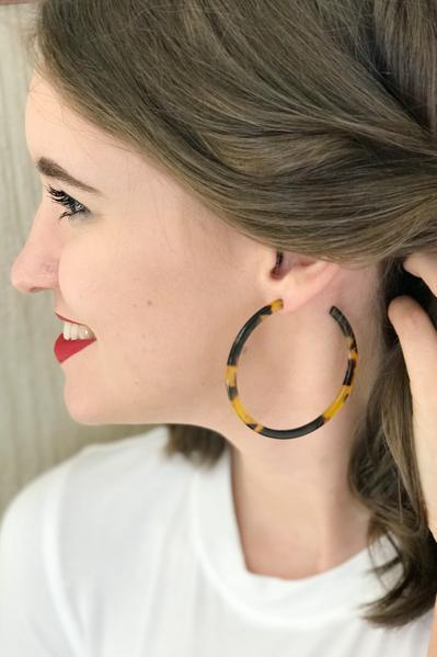 Model wearing brown tortoise hoop earrings