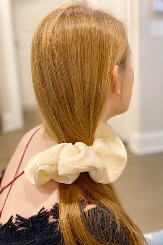 Woman with red hair wearing a ivory silk scrunchie in her side ponytail