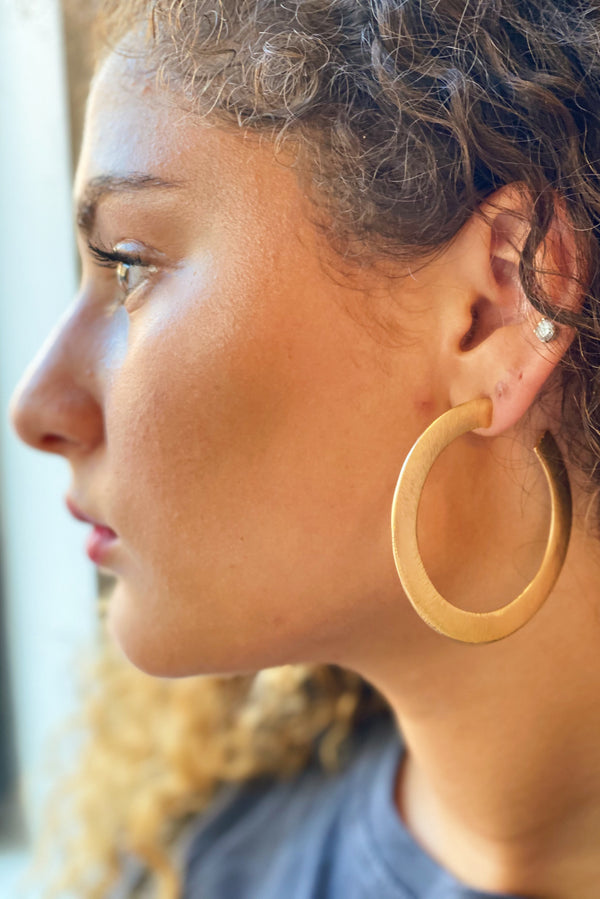 Alma Hoop, Gold shown on a model to showcase the thickness of the hoops.