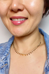 A Chained Twinkling Star Necklace shown on a model. Displays the length of the necklace when wore around your neck.