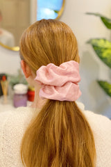 Woman with red hair wearing a dusty pink silk scrunchie in her ponytail
