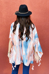Model facing the back wearing the Bright Skies Tie Dye Kimono in Pink showing off the back of the kimono and the tassels on the bottom of the kimono