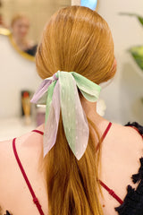 Woman with red hair wearing a green sheer scarf scrunchie in her ponytail