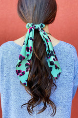 Woman wearing leopard print scarf scrunchie
