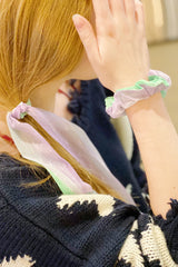 Woman with red hair wearing a green sheer scarf scrunchie on her wrist