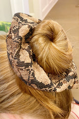close up Woman with red hair wearing a snake skin silk scrunchie in her bun