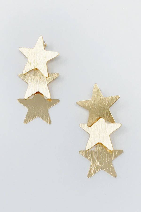 gold star dangling earrings displayed on white background