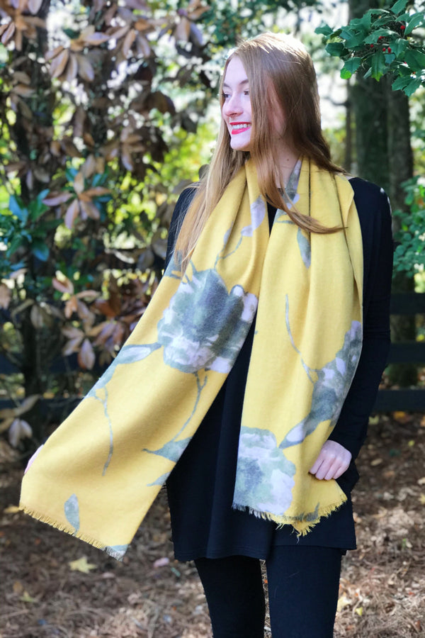 Model wearing a cashmere mustard yellow floral print scarf from online Boutique Ellison + Young
