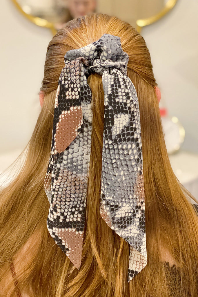 Red headed woman wearing snake skin ponytail scrunchie in her half up half down hair style